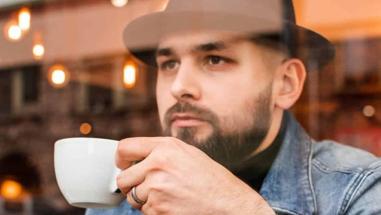 גבר עם זקן יושב בבית קפה לפגישת עסקים
