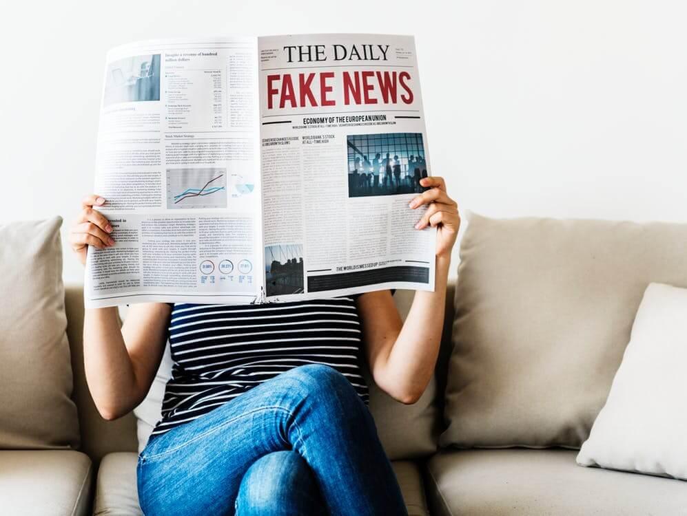 אישה יושבת על ספה וקוראת עיתון שכתוב עליו פייק ניוז