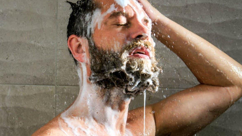 גבר במקלחת עם זקן מלא בסבון