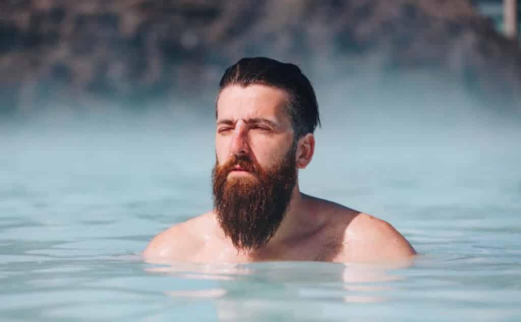 גבר עם זקן מלא וארוך שוחה באגם
