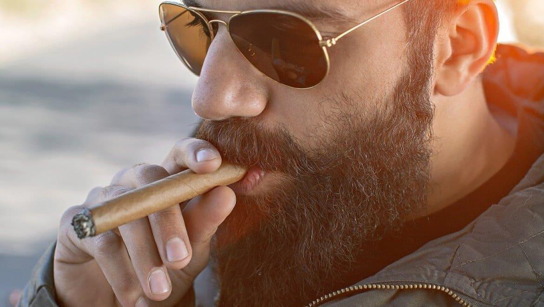 גבר עם זקן מלא מעשן סיגר