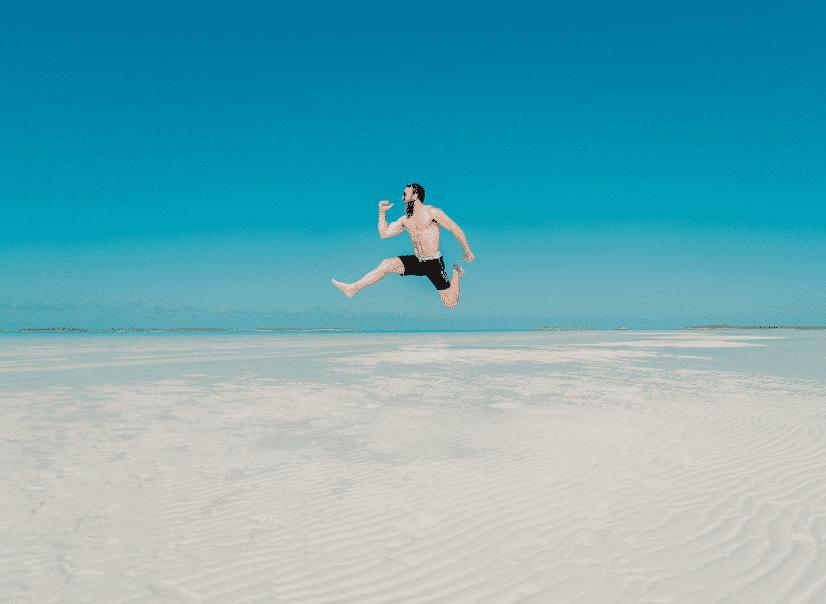 גבר עם זקן קופץ בחוף הים