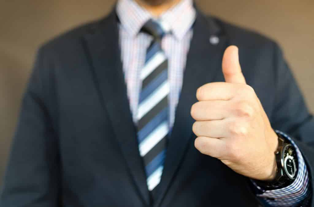 גבר צעיר עם שעון על היד מראה סימן שהכל בסדר