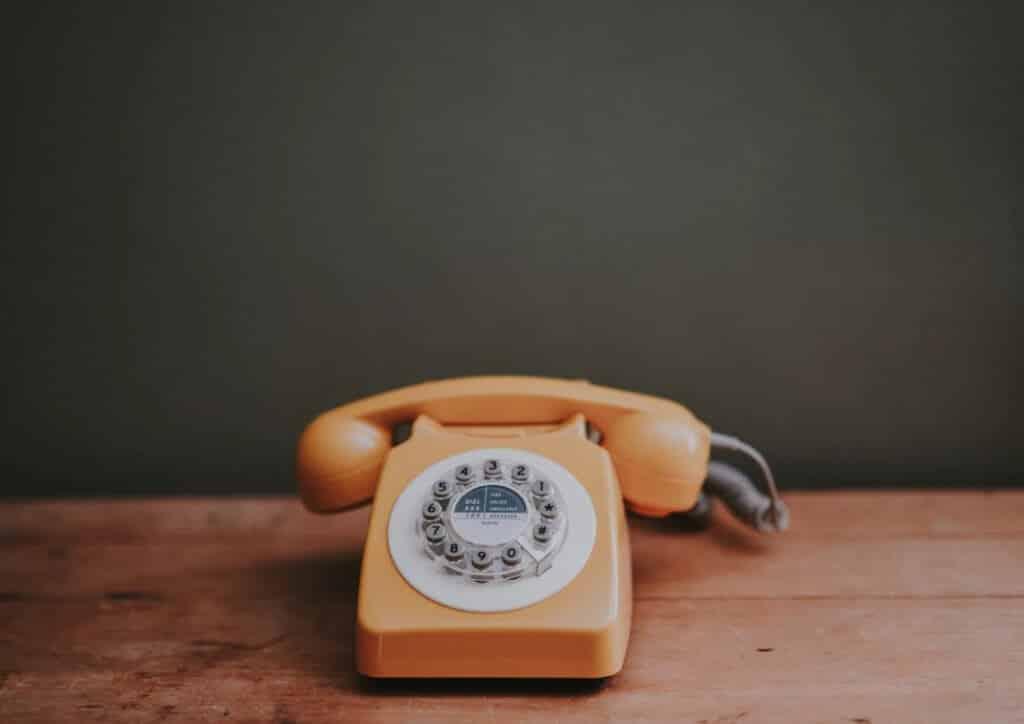 טלפון מחוגה בצבע כתום עומד על שולחן