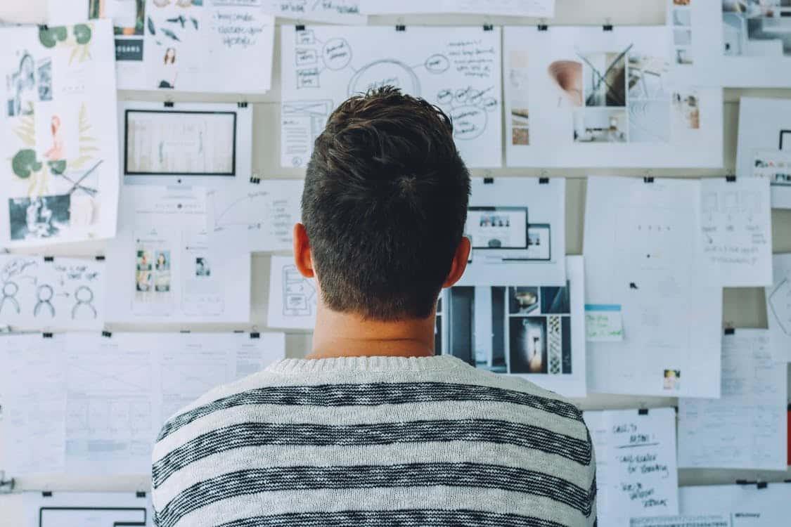 גבר מסתכל על קיר עם הרבה ניירות