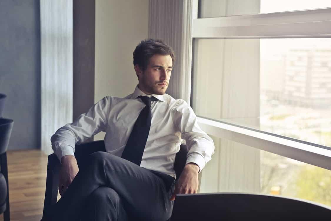 גבר עם שיער מעוצב עם ספריי יושב ומביט מהחלון