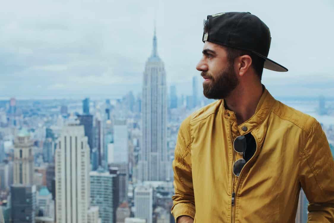 תייר בניו יורק עם זקן וכובע מצחייה הפוך על רקע של בניינים