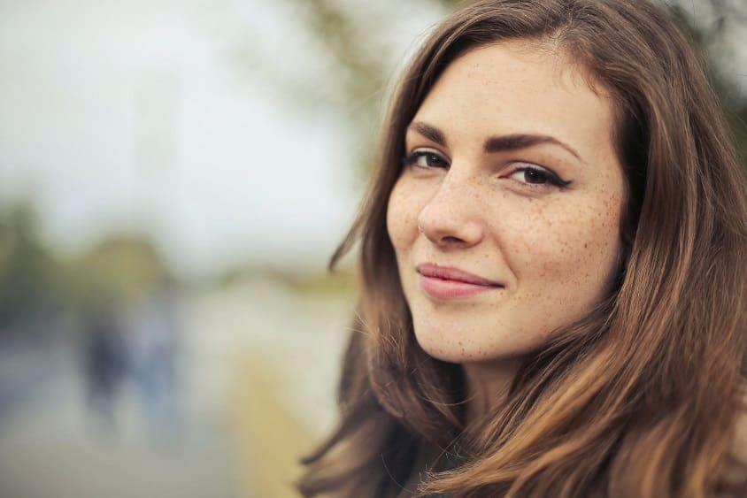 בחורה צעירה עם נמשים מחייכת